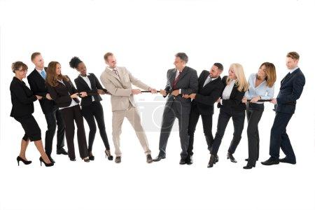 Photo pour Toute la longueur des équipes multi ethniques d'affaires jouant remorqueur de guerre contre fond blanc - image libre de droit