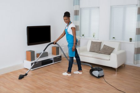 Photo for Young African Woman Cleaning Hardwood Floor With Vacuum Cleaner - Royalty Free Image