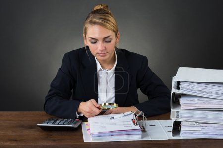 Businesswoman Examining Bills With Magnifying Glass