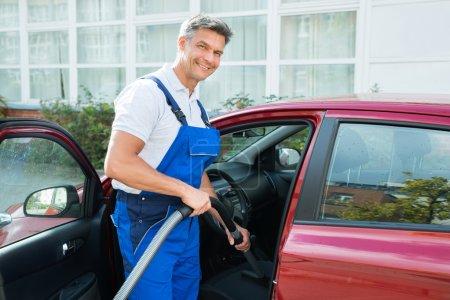 Happy Worker Vacuuming Car Seat