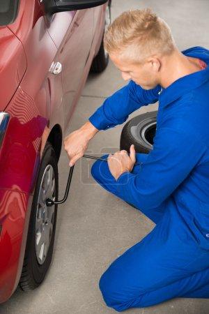Mechanic Changing Tire In Garage