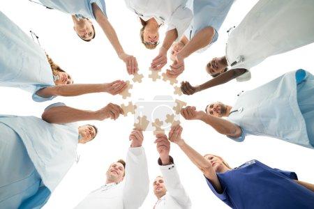Photo pour Directement au-dessous de la photo de l'équipe médicale joignant des pièces de puzzle en câlin sur fond blanc - image libre de droit