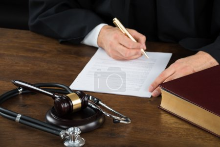 Midsection of judge writing on legal documents wit...