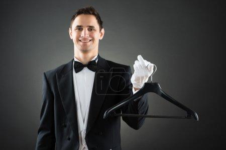 Photo pour Portrait de femme de ménage heureuse tenant le cintre tout en se tenant debout sur fond gris - image libre de droit