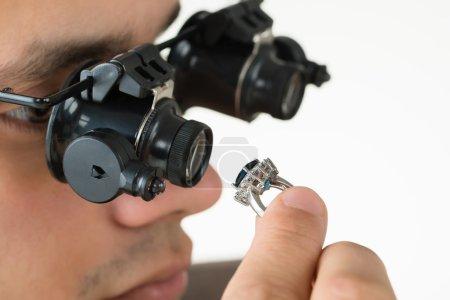 Jeweler Examining Diamond Ring With Magnifying Loupe