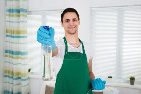 Smiling Cleaner Holding Spray Bottle
