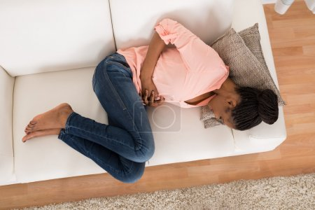 Woman With Stomach Ache Lying On Sofa