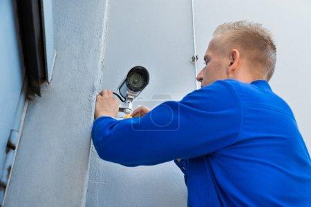 Technician Installing Camera In Corner