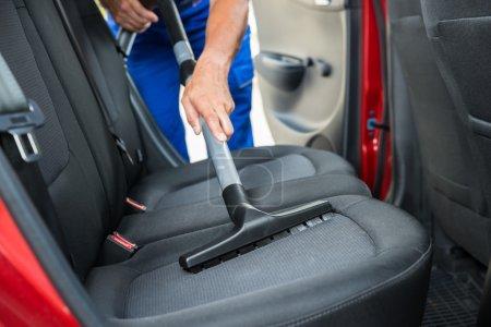 Photo pour Bricoleur aspiration siège arrière de voiture avec aspirateur - image libre de droit