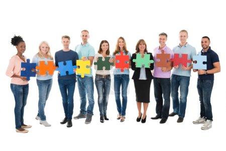 Photo pour Portrait complet de gens d'affaires créatifs tenant des pièces de puzzle sur fond blanc - image libre de droit