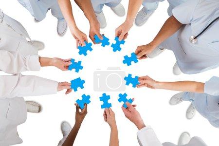 Medical Team Holding Blue Jigsaw Pieces