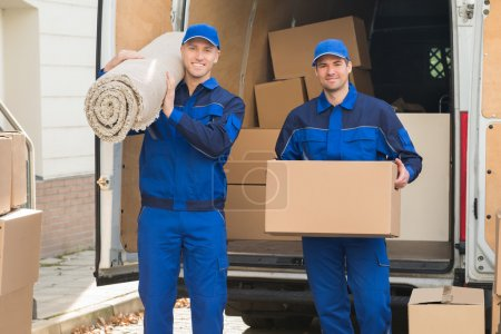 Photo for Portrait of happy delivery men carrying cardboard box and carpet outside van - Royalty Free Image