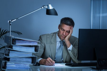 Tired Businessman Writing On Document