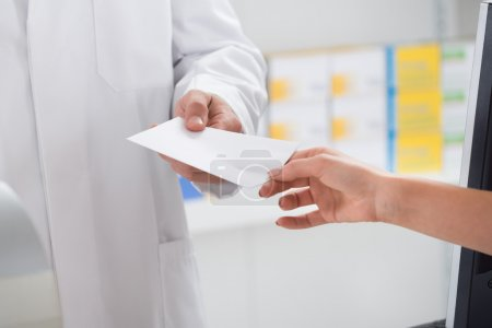 Woman Giving Prescription Paper To Pharmacist