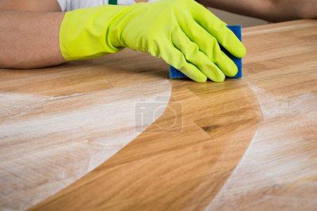 Photo pour Image recadrée de l'homme nettoyant la poussière sur une table en bois à la maison - image libre de droit