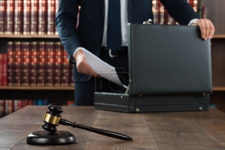 Photo for Midsection of lawyer putting documents in briefcase with gavel at desk in courtroom - Royalty Free Image