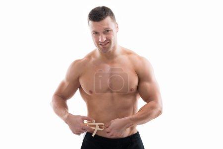 Muscular Man Measuring Fats With Caliper