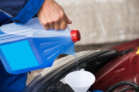 Photo pour Cropped image de liquide lave-glace versant militaire mature en voiture à la station service - image libre de droit
