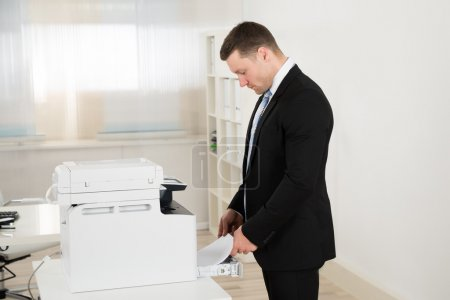 Businessman Inserting Paper In Photocopy Machine