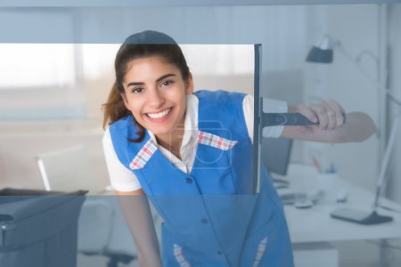 Photo pour Portrait d'une jeune ouvrière souriante nettoyant une vitre avec raclette au bureau - image libre de droit