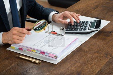 Photo pour Image recadrée d'un homme d'affaires vérifiant la facture avec une loupe au bureau - image libre de droit