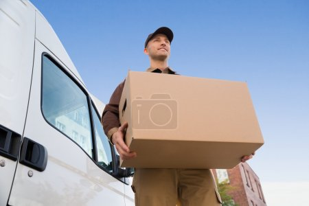 Photo for Low angle portrait of young delivery man carrying cardboard box by truck against sky - Royalty Free Image