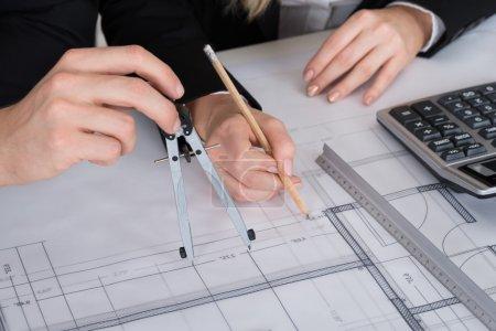 Photo pour Image recadrée de jeunes architectes travaillant sur un plan directeur au bureau - image libre de droit