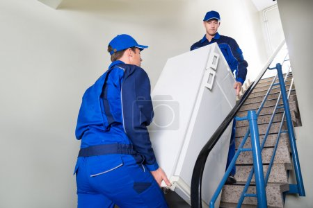 Photo for Side view of movers carrying refrigerator while climbing steps at home - Royalty Free Image