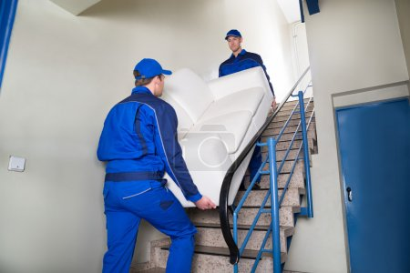 Photo for Male movers carrying sofa while climbing steps at home - Royalty Free Image
