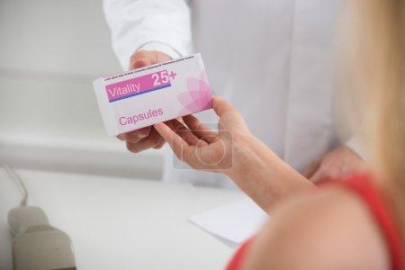 Pharmacist Giving Capsule Packet To Customer