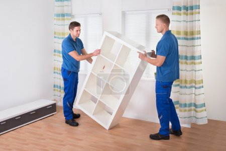 Photo for Young male movers carrying shelf at home - Royalty Free Image