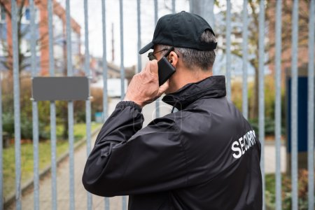 Security Guard Talking On Mobile Phone