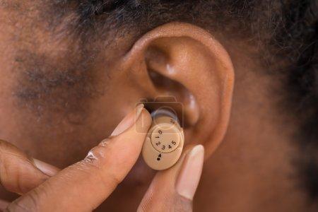 Photo pour Gros plan de femme main mettre la prothèse auditive dans l'oreille - image libre de droit