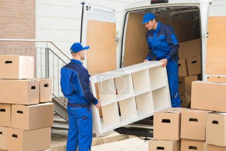 Photo for Young male movers unloading furniture and cardboard boxes from truck on street - Royalty Free Image