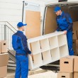 Young male movers unloading furniture and cardboar...