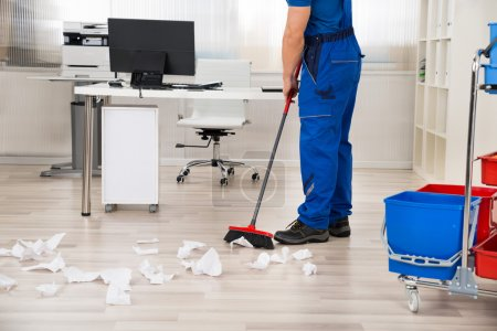 Janitor Sweeping Floor With Broom In Office