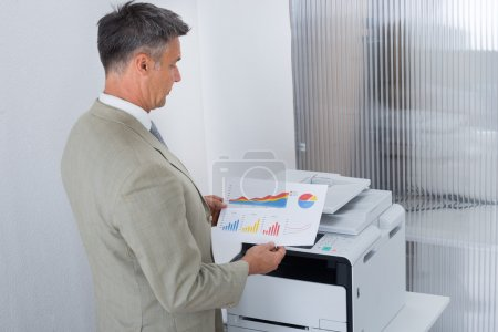 Businessman Looking At Paper With Graphs