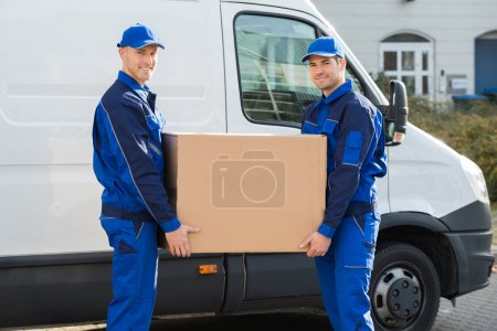 Photo for Portrait of happy delivery men carrying cardboard box while standing against truck - Royalty Free Image
