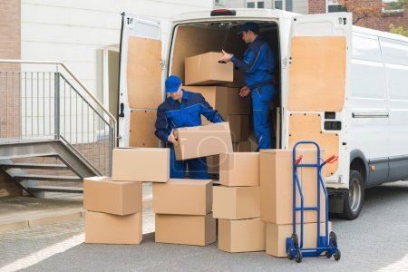 Photo for Young delivery men unloading cardboard boxes from truck on street - Royalty Free Image