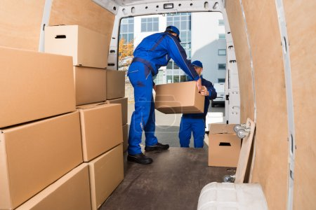 Photo for Young delivery men loading cardboard boxes in truck - Royalty Free Image
