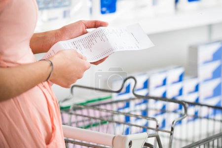 Woman Holding Receipt In Supermarket