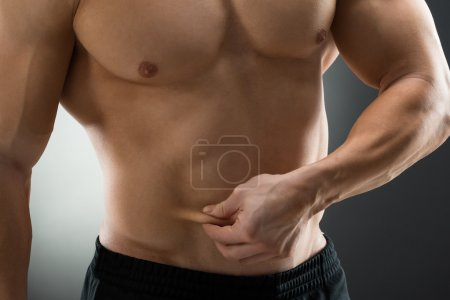 Midsection Of Man Holding Fat Belly
