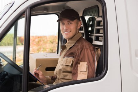 Photo for Portrait of confident delivery man making checklist in truck - Royalty Free Image