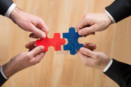 Photo pour Image recadrée d'hommes d'affaires assemblant puzzle représentant le travail d'équipe au bureau - image libre de droit