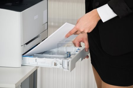 Businesswoman Inserting Papers