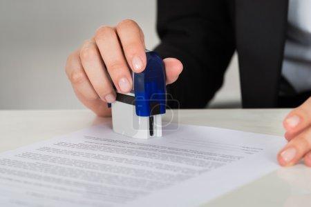 Photo pour Image recadrée d'une jeune femme d'affaires estampillant un document contractuel au bureau - image libre de droit