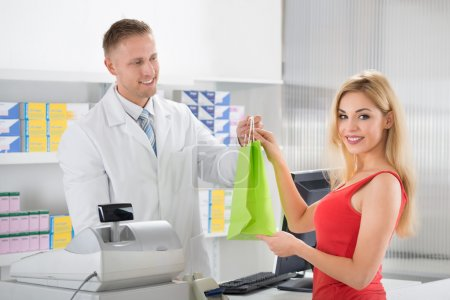 Smiling Pharmacist Giving Medicines