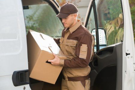 Delivery Man Removing Cardboard Box