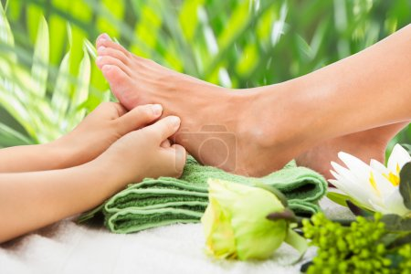 Photo for Cropped image of masseuse massaging woman's foot against leaves at beauty spa - Royalty Free Image