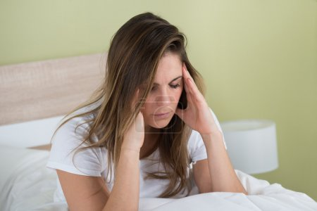 Woman With Headache Sitting On Bed
